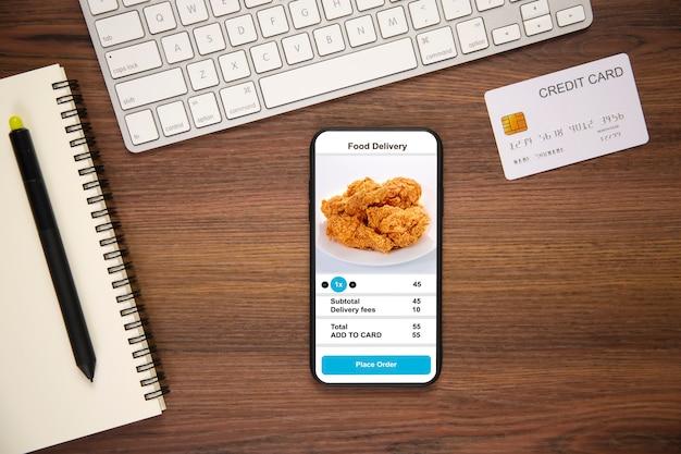 Telefoon vasthouden met voedsel voor bezorging van applicaties Premium Foto