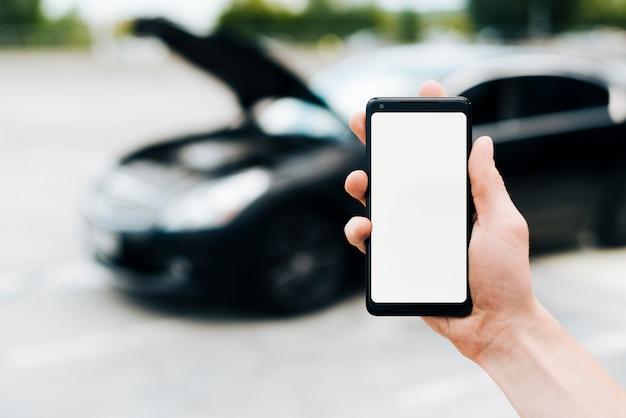 Telefoonmodel met auto op achtergrond Gratis Foto