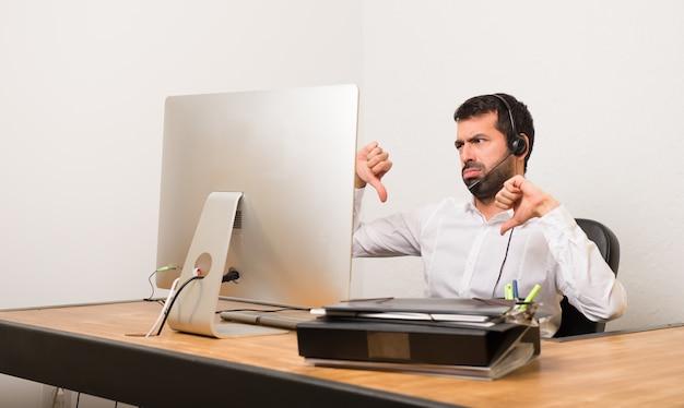 Telemarketer man in een kantoor met duim naar beneden met beide handen Premium Foto