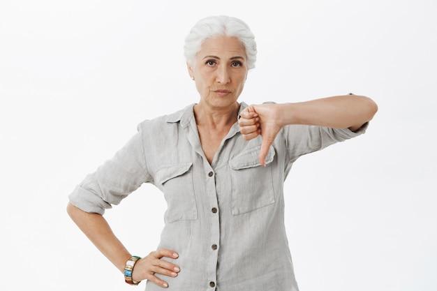 Teleurgestelde grootmoeder met duimen naar beneden en ontevreden grimassen Gratis Foto