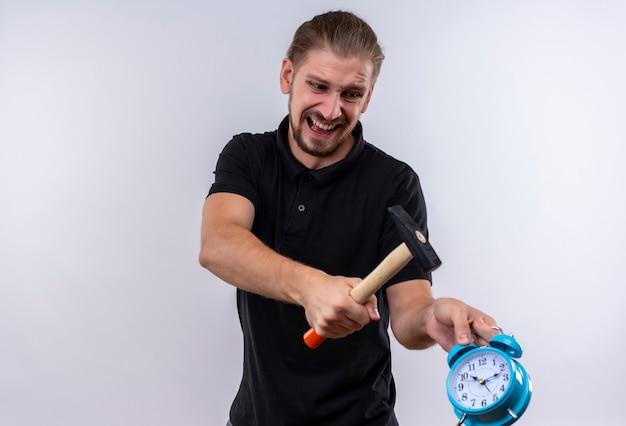 Teleurgestelde jonge knappe man in zwart poloshirt met een hamer gaat wekker in zijn hand breken met agressieve uitdrukking op gezicht staande op witte achtergrond Gratis Foto