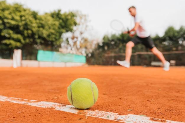 Tennisbal die op de vloer legt Gratis Foto