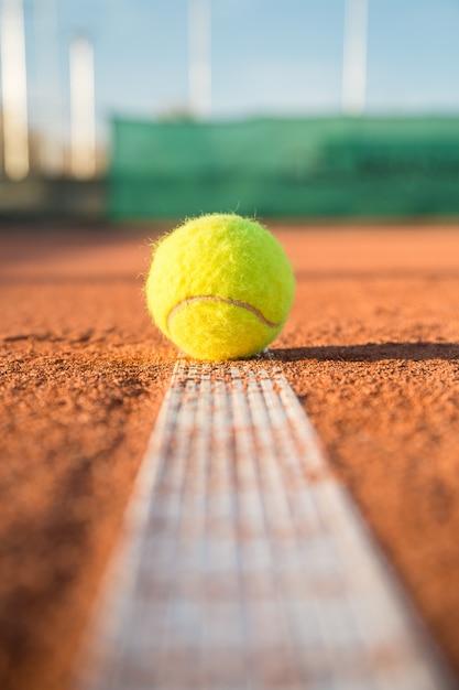 Tennisbal die op witte lijn op tennisbaan op zonnige dag liggen. Premium Foto