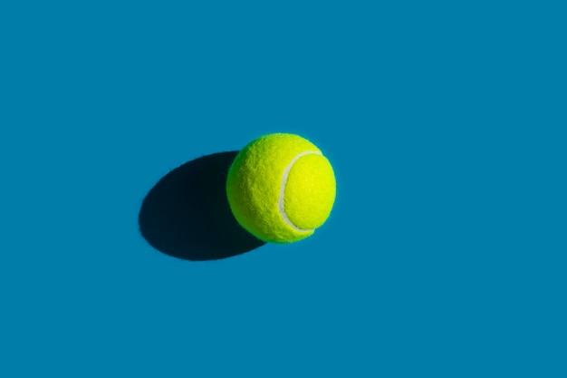 Tennisbal met sterke schaduw op blauw Premium Foto