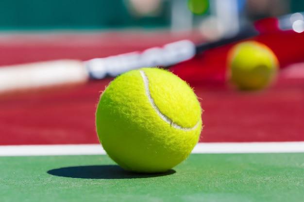 Tennisballen en racket op het grashof Premium Foto