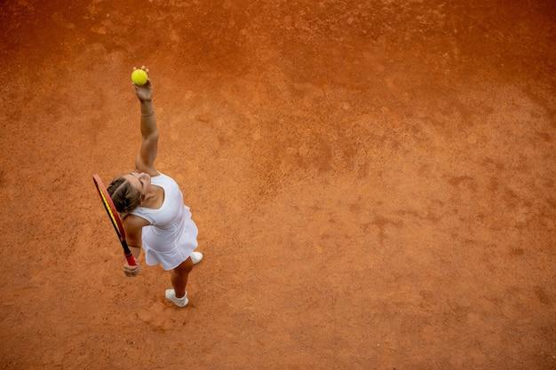 Tennisser in witte sportkleding voorbereiden om tennisbal te dienen, training voor wedstrijd. bovenaanzicht Premium Foto