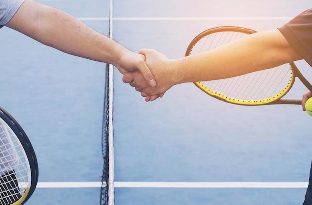 Tennisspelers die hand schudden vóór gelijke op tennisbaan Gratis Foto