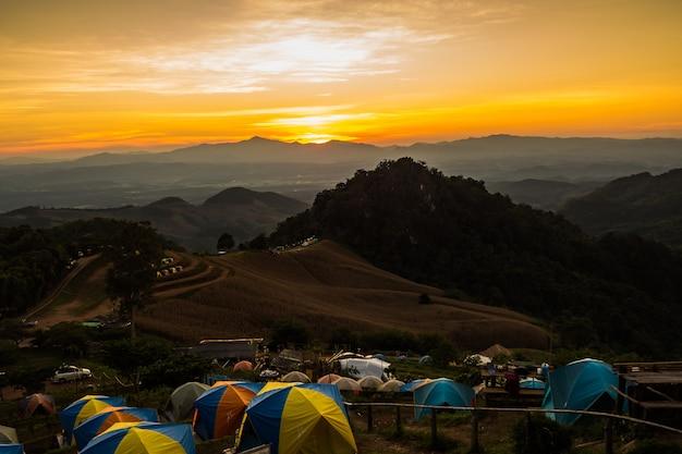 Tent in de zonsondergang met uitzicht op bergen Premium Foto