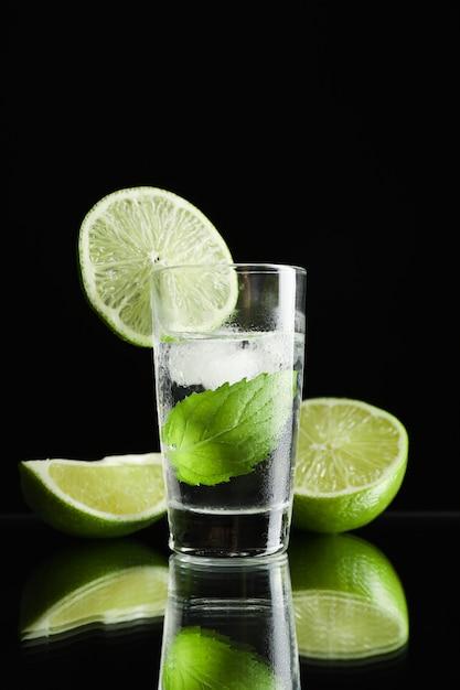 Tequila geschoten met limoen, munt en ijs tegen zwart Premium Foto