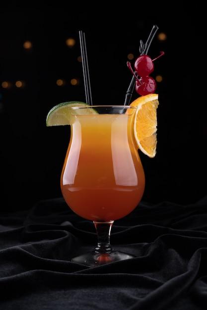 Tequila sunrise cocktail, op een zwarte ondergrond Premium Foto