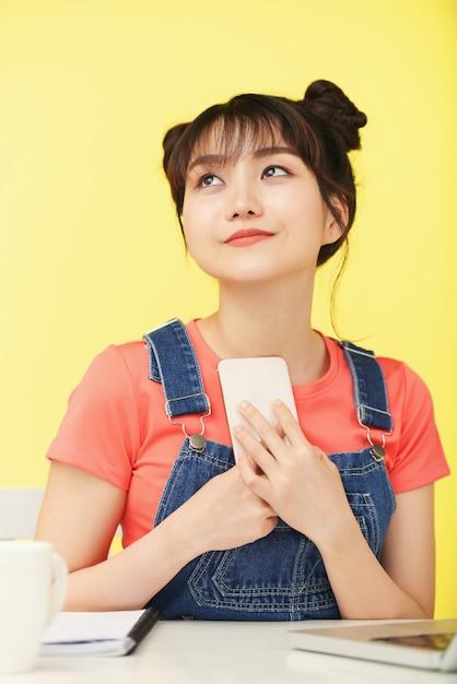 Terloops geklede aziatische vrouw die bij bureau zit, omhoog kijkt en smartphone omklemt naar de borst Gratis Foto