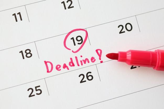 Termijn schrijven op witte kalenderpagina datum close-up Premium Foto