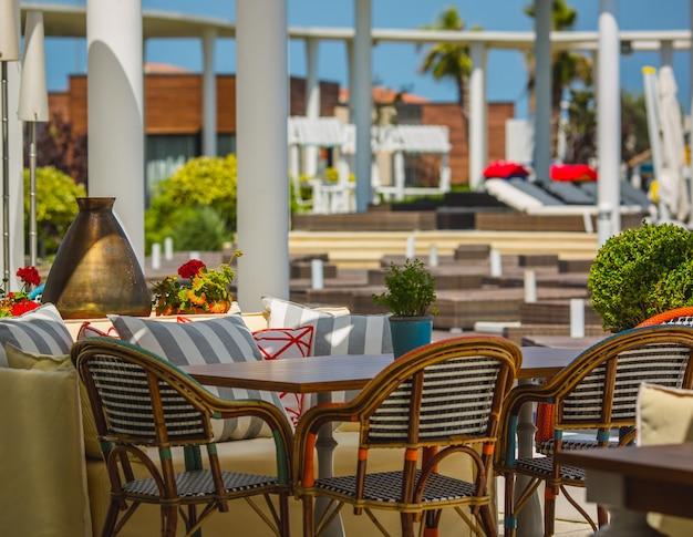 Terras van een hotel gevuld met zachte meubels in een groene ruimte. Gratis Foto