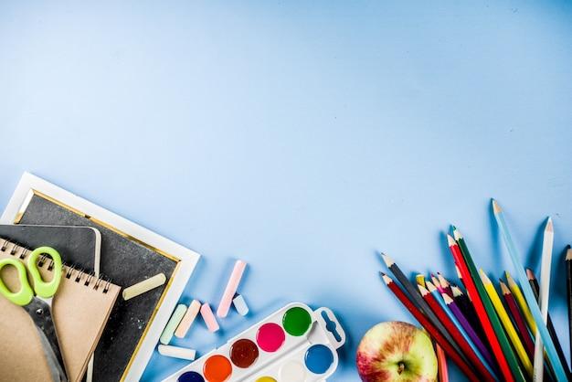 Terug naar school achtergrond met accessoires voor het schoollokaal - verven, potloden, schriften, boeken, schaar, krijt, stiften, blauwe achtergrond, boven exemplaarruimte Premium Foto
