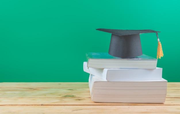 Terug naar school . afstuderen cap met boeken op tafel Premium Foto