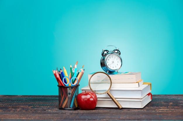 Terug naar school concept. boeken, kleurpotloden en klok Gratis Foto