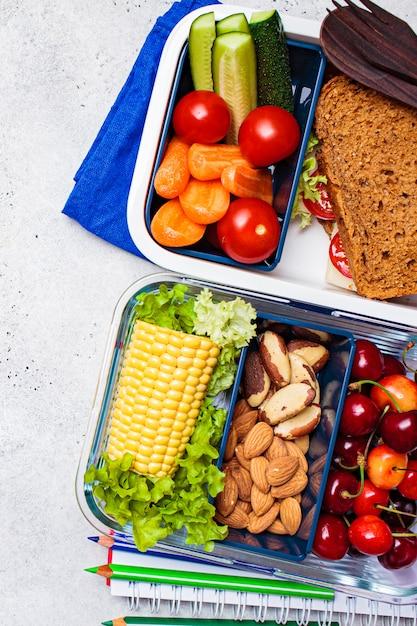 Terug naar school-concept. lunchbox met gezond vers voedsel. sandwich, groenten, fruit en noten in voedsel container, lichte achtergrond. Premium Foto