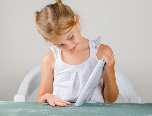 Terug naar school concept zijaanzicht. klein meisje kijken naar boekomslag. Gratis Foto