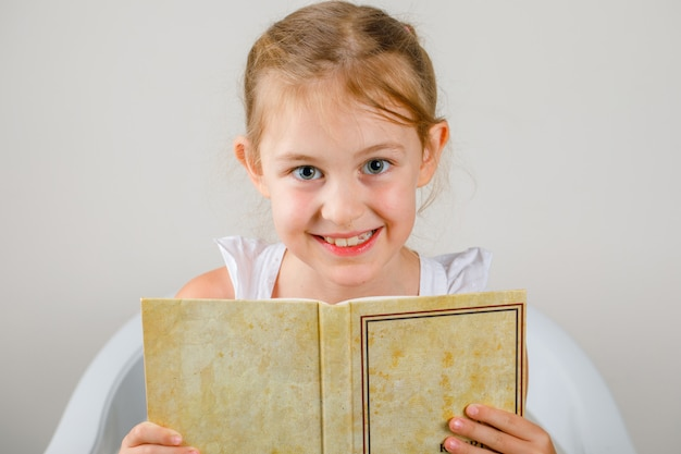 Terug naar school concept zijaanzicht. meisje zitten en houden boek. Gratis Foto