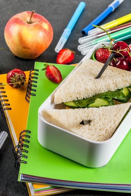 Terug naar school. een stevige gezonde schoollunch in een doos: broodjes met groenten en kaas, bessen en fruit (appels) met notitieboekjes, gekleurde pennen op een zwarte tafel. Premium Foto