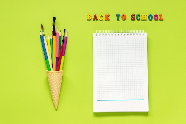 Terug naar school en kleurpotlodenpenseel in wafelroomijskegel en notitieboekje op groene achtergrond. Premium Foto