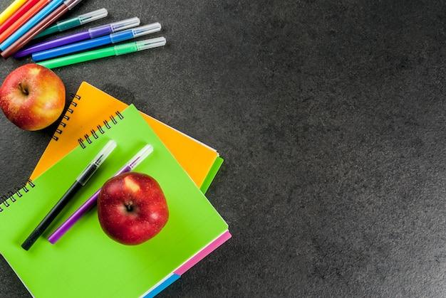 Terug naar school. fruitappels met notitieboekjes, gekleurde pennen op een zwarte tafel. copyspace bovenaanzicht Premium Foto