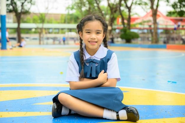 Terug naar school. gelukkig lachend meisje van basisschool op het schoolplein. Premium Foto