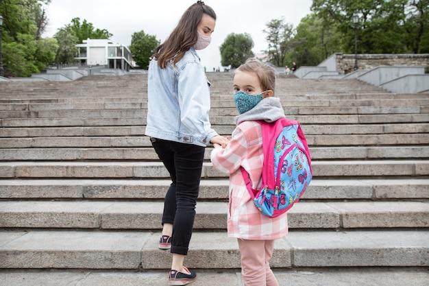 Terug naar school. kinderen met een coronavirus-pandemie gaan met maskers naar school. vriendschappelijke betrekkingen met mijn moeder. Gratis Foto