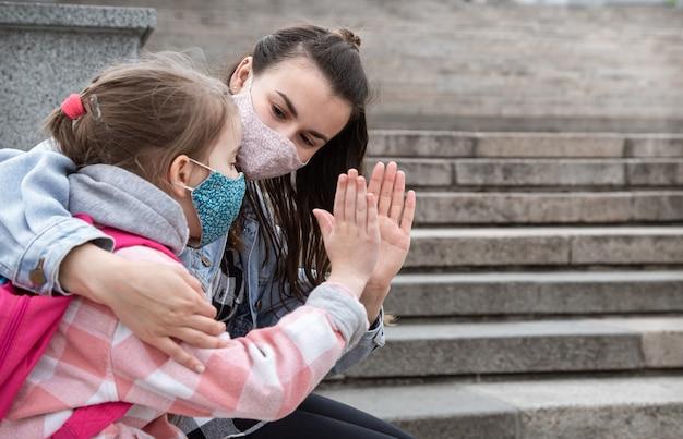 Terug naar school. kinderen met een coronavirus-pandemie gaan met maskers naar school. vriendschappelijke betrekkingen met moeder. kinderopvoeding. Gratis Foto