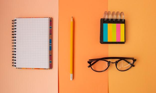 Terug naar school kladblok in geruite potloodglazen bovenaanzicht Premium Foto