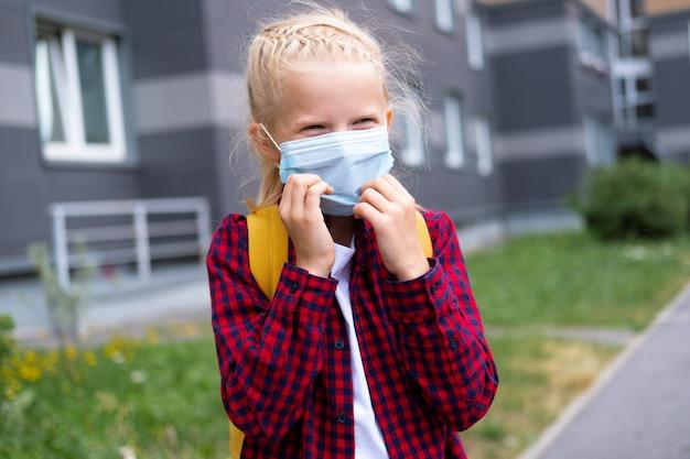 Terug naar school. meisje met masker en rugzakken beschermt en beschermt tegen coronavirus. kind gaat naar school nadat de pandemie voorbij is. Premium Foto