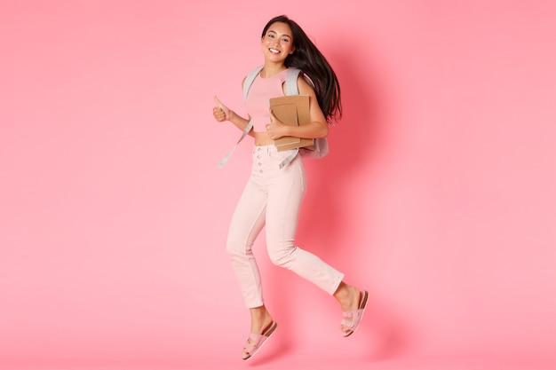 Terug naar school, onderwijs en levensstijlconcept. volledige lengte van gelukkige glimlachende aziatische vrouwelijke student, meisje van universiteit die met notitieboekjes en rugzak springt, duimen-omhoog toont in goedkeuring, roze muur Gratis Foto