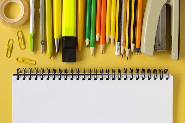 Terug naar school . open lege mockup notebook en gekleurde school briefpapier. geel papier achtergrond. Premium Foto