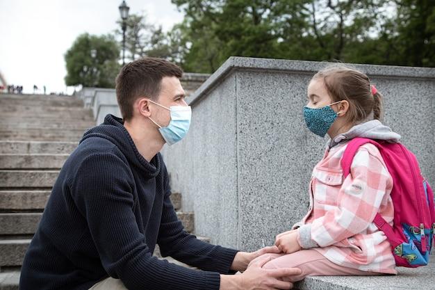 Terug naar school, pandemie. jonge vader en dochtertje in een masker. vriendelijke familierelaties. Gratis Foto