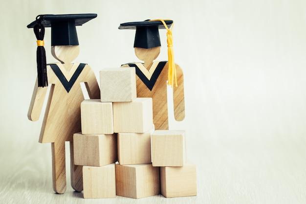 Terug naar school, studenten ondertekenen hout afstuderen viert cap met houten vierkante blokken Premium Foto