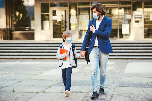 Terug naar school tijdens coronavirus-pandemie. vader die zoon naar school brengt. Premium Foto