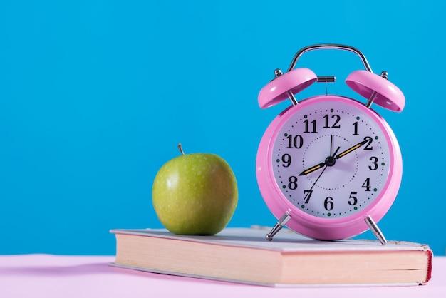 Terug naar schoolachtergrond met boeken, apple en wekker Gratis Foto