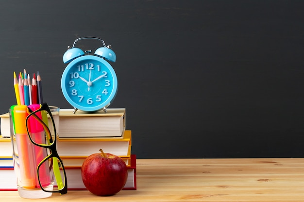 Terug naar schoolappel en boeken met potloden en oogglazen over bord. Premium Foto