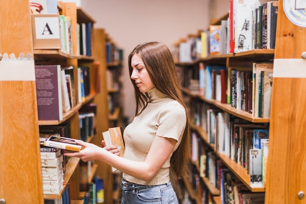 Terug naar schoolconcept met vrouw die in bibliotheek bestudeert Gratis Foto