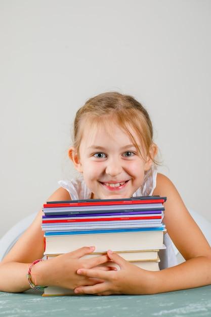 Terug naar schoolconcept op pleister en grijs muur zijaanzicht. klein meisje knuffelen schriften en boeken. Gratis Foto