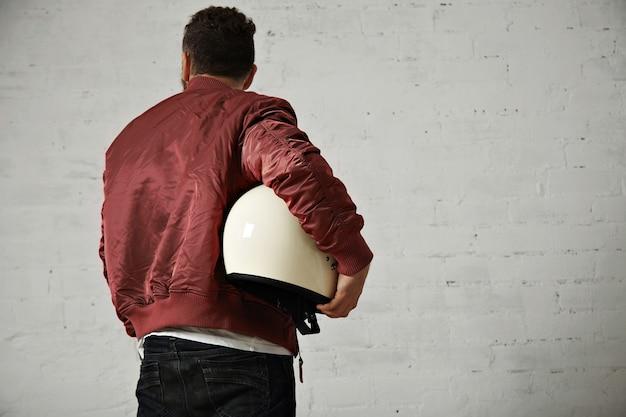 Terug shot van een man in spijkerbroek, korte terracotta jasje met een sprankelende witte motorhelm onder zijn arm geïsoleerd op wit Gratis Foto
