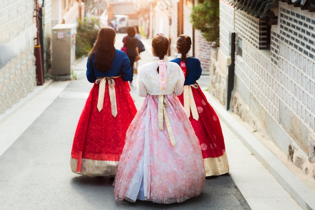 Terug van drie vrouw die hanbok draagt die door het dorp van bukchon hanok in seoel, zuiden loopt Premium Foto