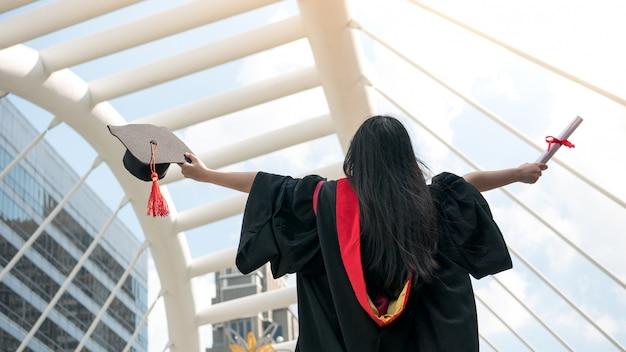 Terug van meisje in zwarte toga's en houd diploma-certificaat met gelukkig afgestudeerd. Premium Foto