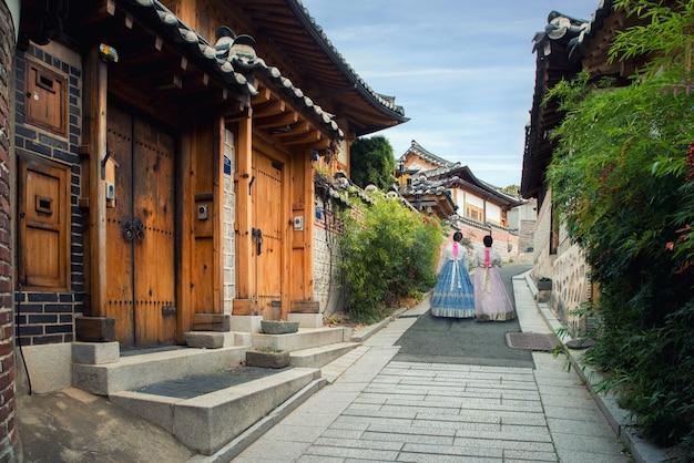 Terug van vrouw twee die hanbok draagt lopend in het dorp van bukchon hanok in seoel, zuid-korea. Premium Foto