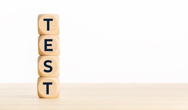 Test concept. houten blokken met tekst op bureau. kopieer ruimte Premium Foto