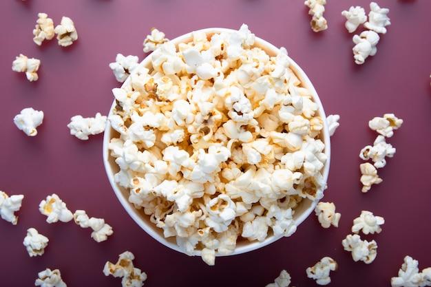 Testy warme popcorn van bovenaf op rode achtergrond bekeken Premium Foto