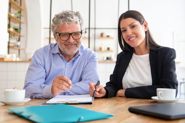Tevreden agent en klant ontmoeten elkaar tijdens een kopje koffie bij co-working, zittend aan tafel, documenten bekijken, Gratis Foto