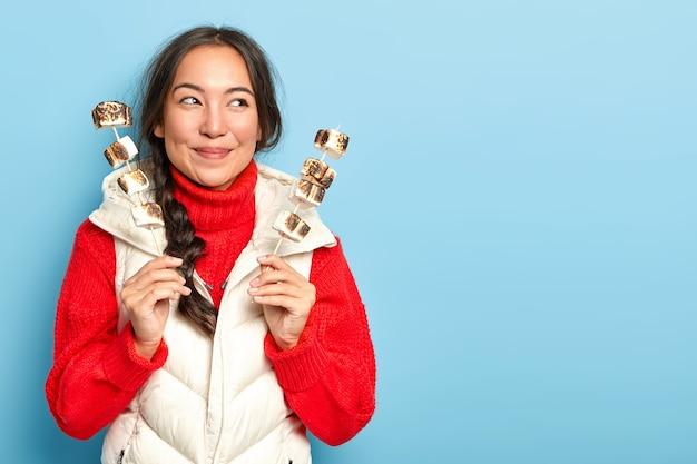 Tevreden aziatisch meisje houdt geroosterde marshmallow op kampvuur, stelt zoete traktatie voor, brengt zondag door op picknick in het bos, draagt warme rode gebreide trui en wit vest, geïsoleerd op blauwe muur Gratis Foto