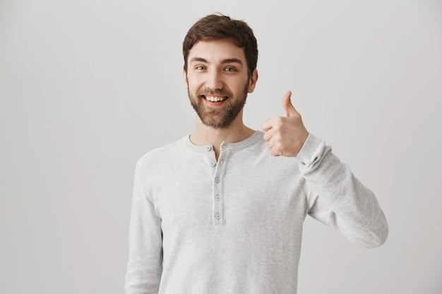 Tevreden, bebaarde mannelijke klant toont goedkeuring met duim omhoog Gratis Foto