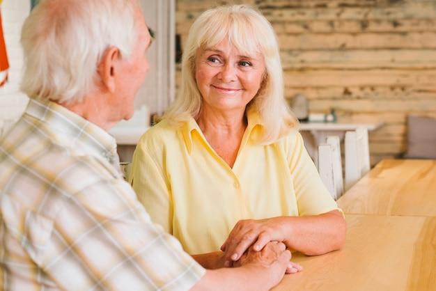 Tevreden bejaarde echtpaarzitting in koffie en hand in hand Gratis Foto